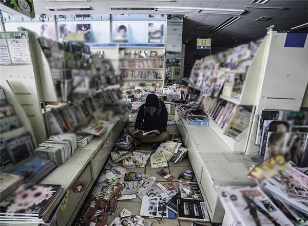 Nhiếp ảnh gia đọc sách trong một hiệu sách bỏ hoang.
