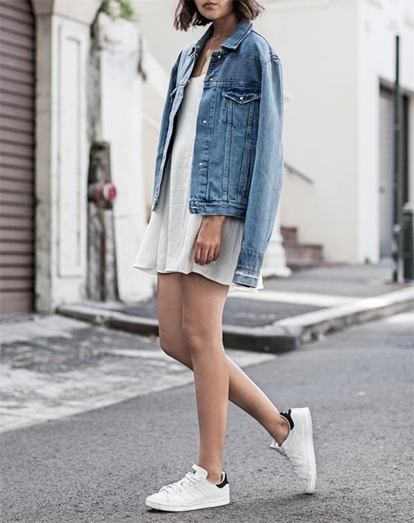 """Thêm một gợi ý hay ho để tận dụng chiếc áo khoác denim là combo đầm trơn 2 dây diện cùng sneaker trắng. Bộ cánh tuy có vẻ """"bánh bèo"""" nhưng nhờ giày sneaker nó trở nên cá tính và thoải mái hơn bao giờ hết."""
