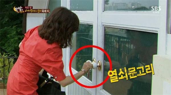 """Trong """"Đôi tai ngoại cảm"""", nhân vật Lee Bo Young loay hoay dùng chìa khóa để mở cửa."""