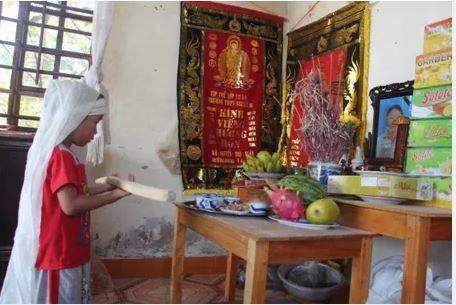 Đứa em trai út của Huyền bên bàn thờ mẹ. Ảnh: Internet