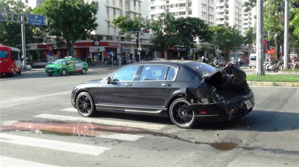 Một chiếc Bentley bị xe container từ sau húc tới, tông nát đuôi khi vừa dừng chờ đèn đỏ tại giao lộ Nguyễn Văn Linh - Nguyễn Đức Cảnh, Q.7, TP.HCM sáng 2-6.(Ảnh: Lê Phan)