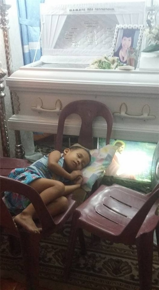 Cậu bé ngủ trên ghế gần quan tài của mẹ.