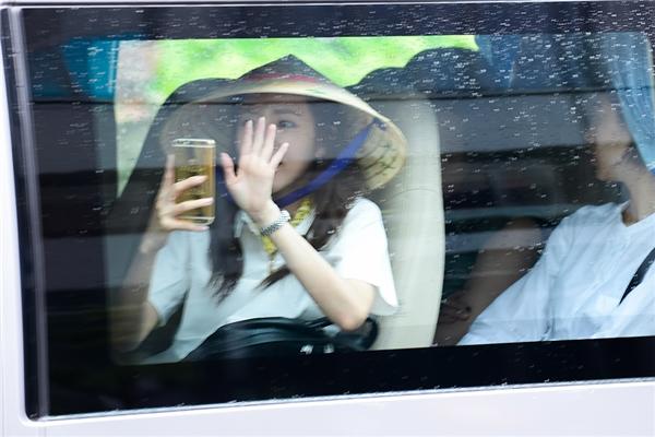 Dù đã lên xe nhưng Dara vẫn dùng điện thoại để chụp ảnh các bạn fan đang đội mưa và chạy theo thần tượng.