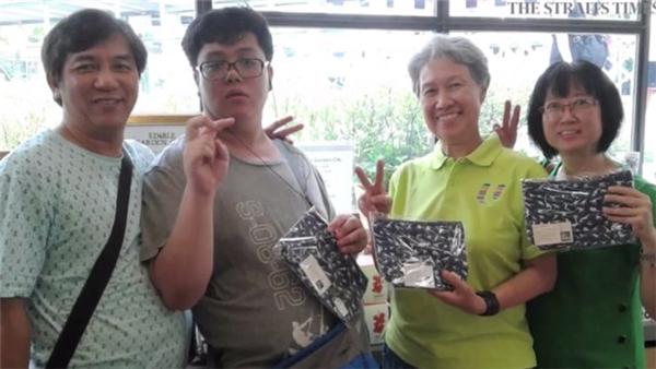 Bà Hà Tinh (thứ hai từ phải) trong buổi mua gây quỹ. Bà đã mua bóp với thiết kế của See Toh Sheng Jie (thứ hai từ trái).(Ảnh: STRAITSTIMES)