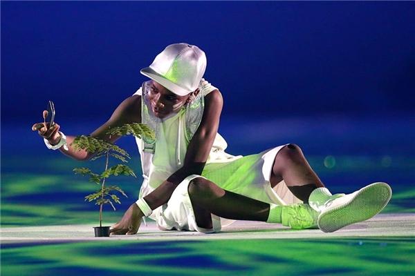 """Trong bức ảnh, một cậu bé đang chụp ảnh tự sướng cùng với chậu cây nhỏ. Cây non này chínhlà biểu tượng cho sự nghiệp trồng rừng cực kì quan trọng của toàn dân tộc Brazil, vì thế mà trong không khí hân hoan của buổi khai mạc thế vận hội Olympic 2016, """"thành viên"""" này nhất định phải có mặt."""