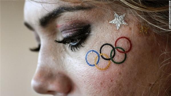 Một khán giả tình nguyện dán lên mặt mình biểu tượng 5 vòng màu để cỗ vũ tinh thần cho các vận động viên khi bị trận đấu bị cơn bão hoãn lại.