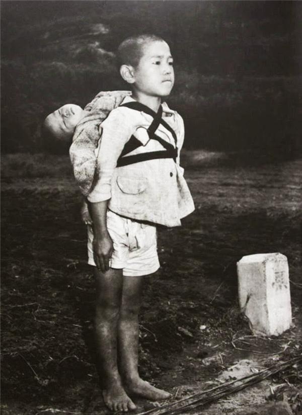Một cậu bé cắn răng đến chảy máu để kiềm lại giọt nước mắt khi đưa em mình nơi thiêu hủy.