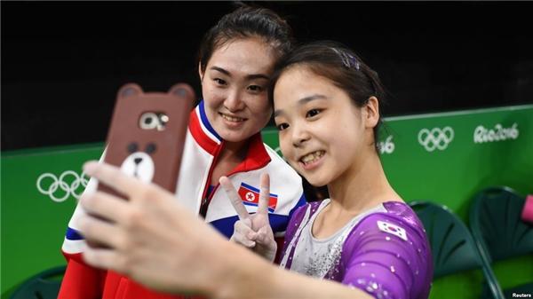 Hãng thông tấn Reuters đã ghi lại được khoảnh khắc 2 nữ VĐV vui vẻ chụp hình cùng nhau. (Ảnh:Reuters)