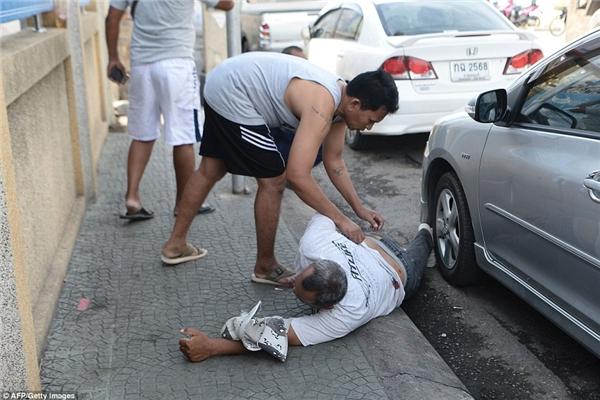 Một người đàn ông bất tỉnh trên vỉa hè sau vụ nổ ở Hua Hin.(Ảnh: Daily Mail)