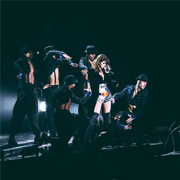 """Chiếc quần này khiến người hâm mộ của cô nàng vô cùng bất ngờvì đây chính là chiếc quần mà các nghệ sĩ Muay Thái thường mặc khi thi đấu. Selena đã biết cách """"lấy lòng"""" người hâm mộ Thái Lan khi diện chiếc quần này trong chuyến lưu diễn. Kết hợp với áo khoác dài và boots cao cá tính, Selena trông cực kì thời trang và trẻ trung."""
