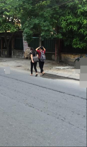 Hai cô bạn với mỗi người một chiếc dép tung tăng đi trên đường. (Ảnh: Beat.vn)