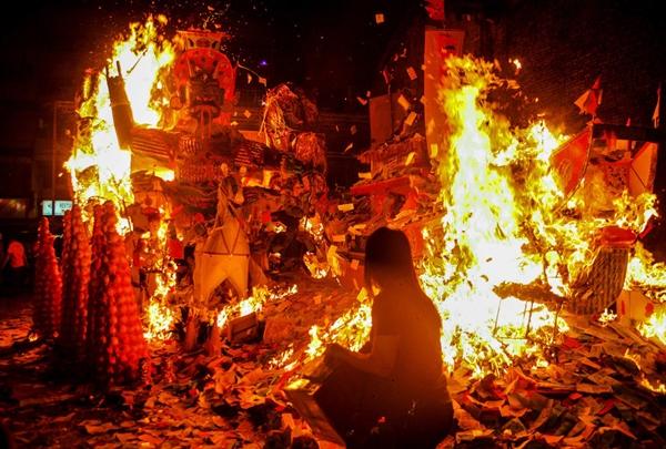 Một người phụ nữ đang ném vàng mã lên 1 ngọn lửa trong lễ cũng cô hồn (the Hungry Ghost Festival) ởKuala Lumpur, Malaysia. Lễ cúng cô hồn rơi vào ngày 15 tháng 7 âm lịch. Theo tín ngưỡng của người Trung Quốc cổ xưa, tháng 7 âm lịch là ngày các linh hồn trở lại dương gian.