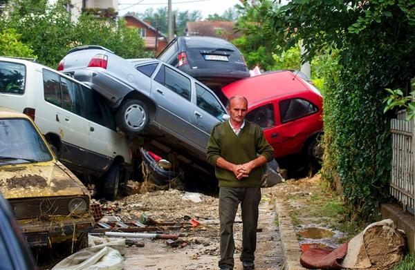 Một người đàn ông đangđi qua đống xe bị hỏng hócdo những đợtcàn quét dữ dội của các cơn bão gần đây tạilàng Stajkovci, Macedonia.Những trận mưabão khốc liệt đã giết chết ít nhất 20 người ở thủ đô Skopje của Macedonia.