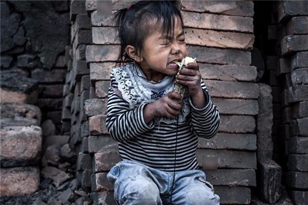 Bé gái nàyđang ăn ngon lànhkhúc mía thừa của ai đó vứt đi.