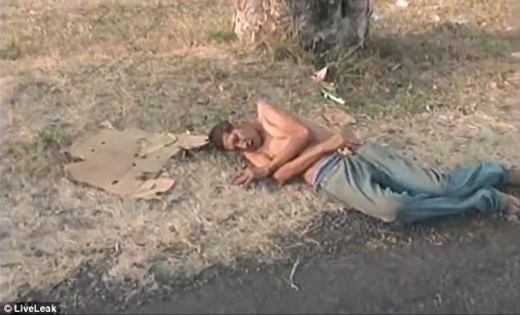 Sau khi bị xe tải đâm, người đàn ông được một vài người khiêngsang bên vệ đường.