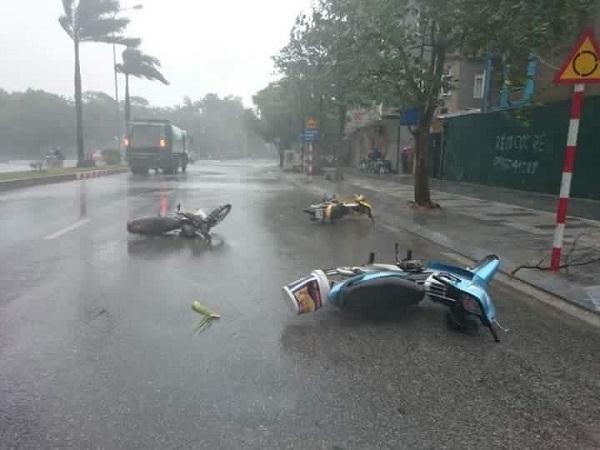 Xe máy ngã rạp ra đường vì sức gió mạnh (Ảnh: TTXVN).