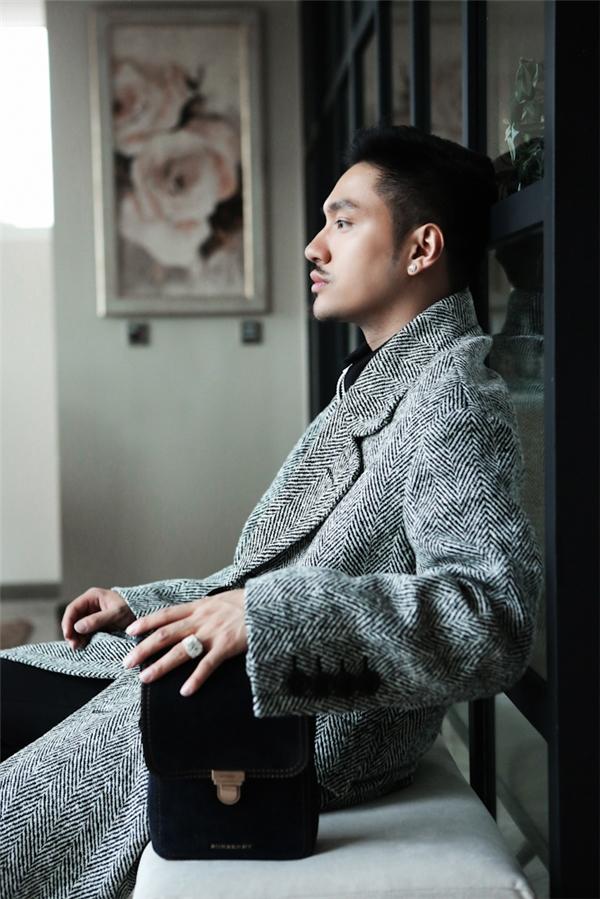 Ngoài vẻ sang trọng,Lý Qúi Khánh còn mang nétcổ điển khi kết hợp áo măng tôvới những phụ kiện đắt tiền.