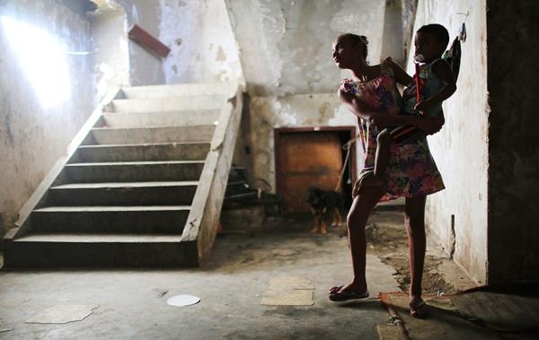 Một cô gái đang bếđứa em trai ở hành lang bên ngoài căn hộ của họ trong cộng đồng Favela Mangueira ở Rio de Janeiro.Phần lớn cộng đồng nàycư trú ở nơicáchkhoảng 1km từsân vận động Maracana, nơi diễn ralễ khai mạc và bế mạc Olympic Rio 2016. Có khoảng 1,4 triệu dân, tương đương khoảng 22% dân số của Rio, cư trú tại Favela, mộtnơi không đảm bảo vệ sinh, thiếu thốn sựchăm sóc y tế, giáo dục và an ninh do băng đảng và bạo lực cảnh sát.Hàng trăm cư dân sống xung quanh khu vực nàyphải ra ngoài lấy nước vì trong tòa nhà không có trang bị hệ thống ống nước.
