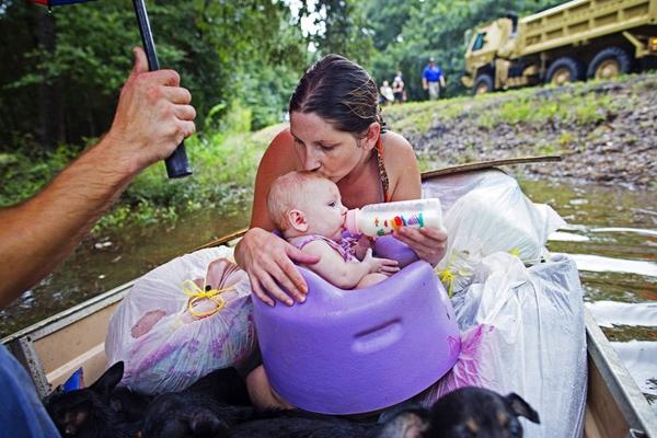 Danielle Blount ở bangLouisiana, Hoa Kỳ, hôn đứa con 3 tháng tuổi của cô ấy trong khi đợi các thành viên của Lục quân Vệ Binh Quốc gia đến giải cứu sau một cơn mưa khủng khiếp nhấn chìm cảLouisiana.
