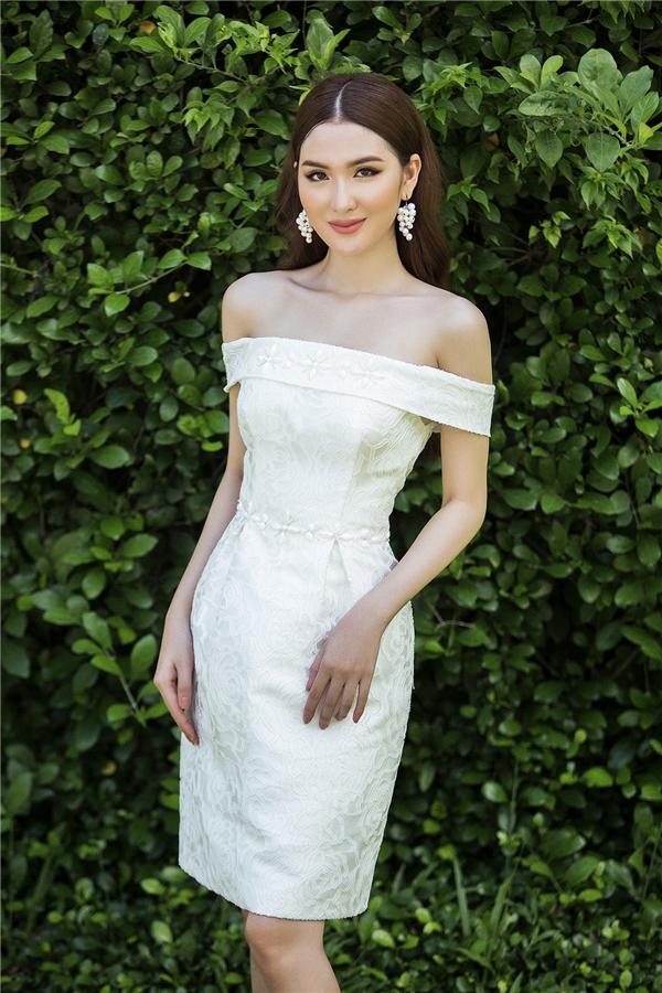 Trên nền sắc trắng cùng phom váy trễ vai cổ điển, họa tiết hoa thoắt ẩn thoắt hiện kết hợp chi tiết đính kết tạo nên một bức tranh giao mua2 sinh động, bắt mắt.