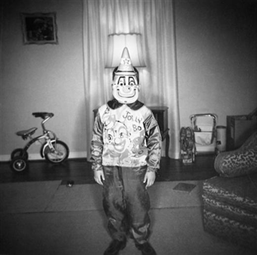 Một cậu bé đeo chiếc mặt nạ hề đang cười toe toét đứng chụp ảnh kỷ niệm trong phòng khách trước khi tham dự lễ hội Halloween năm 1948.