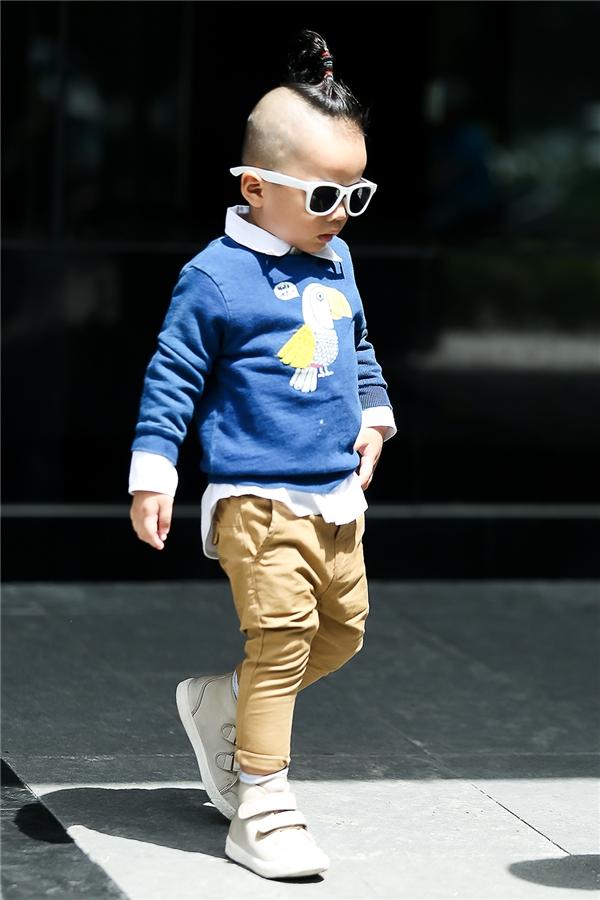Cậu bé diện quần kaki màu be kết hợp sơ mi trắng, áo phông xanh bên ngoài trông vô cùng đáng yêu. Nhím trông vui tươi, lạ mắt hơn khi được bố Đỗ Mạnh Cường phối bộ trang phục cùng mắt kính to bản.