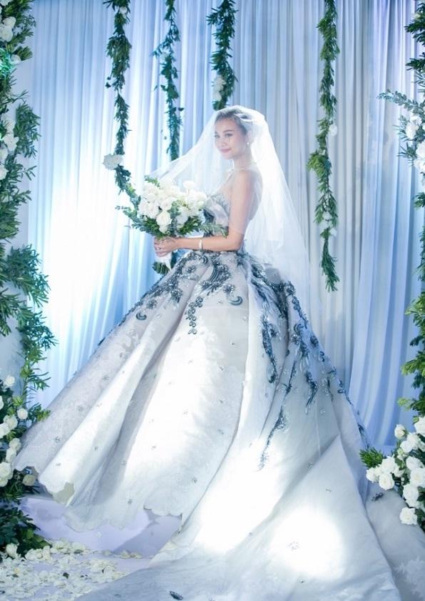 """Mới đây, trên trang Instagram, Thanh Hằng vừa đăng tải hình ảnh cô đeo nhẫn kèm bó hoa trắng khiến khán giả, người hâm mộ """"đứng ngồi không yên"""" bởi nhiều thông tin đồn đoán Thanh Hằng chuẩn bị lên xe hoa. Kèm theo đó là bức ảnh cô mặc váy cưới đứng giữa khung cảnh tràn ngập hoa lá vô cùng lãng mạn."""