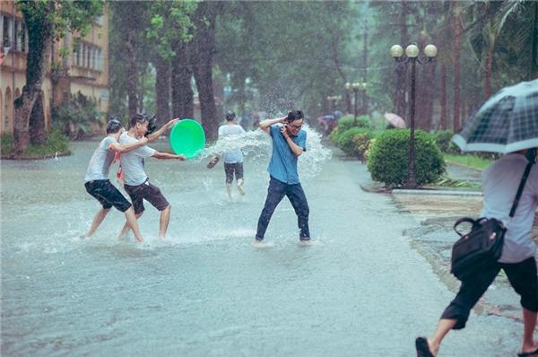 """Tận dụng cơn mưa lớn, các bạn trẻ thỏa sức """"vẫy vùng"""" trong không gian rộng rãi tại sân trường.(Ảnh: NVCC)"""