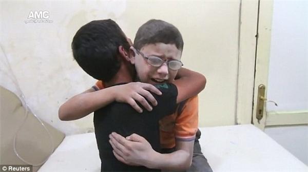 Hình ảnh khiến cả thế giới chết lặng: hai cậu bé Syria ôm nhau khóc nấc vì mất đi người anh em sau trận không kích hôm24/8. (Ảnh: Reuters)