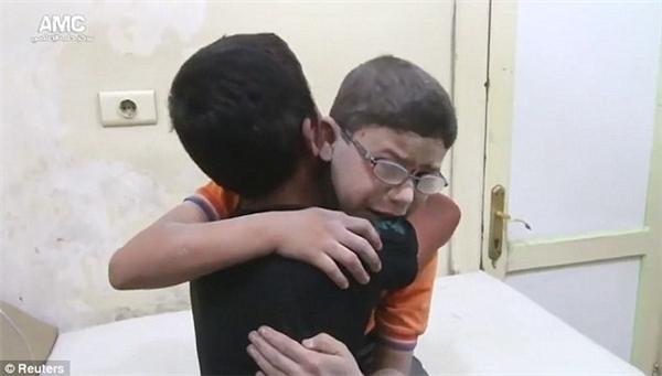 Gương mặt cậu bé tràn ngập nỗi đau xé lòng không thể diễn đạt bằng lời.(Ảnh: Reuters)