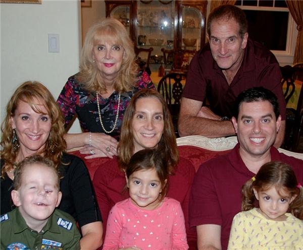 Ethanmỉm cười hạnh phúc khi chụp ảnh với gia đình mình.
