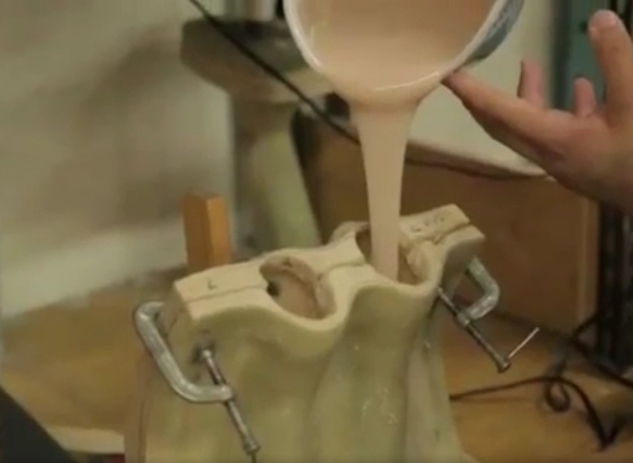 Nhân viên đổ silicone vào khuôn tạo hình búp bê.