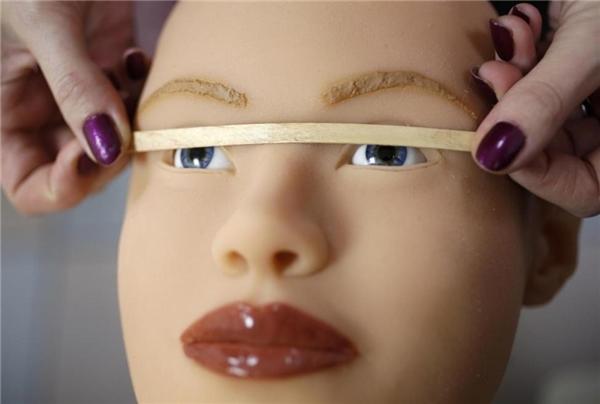 Một nhân viên đangkiểm tra xem mắt của búp bê này đã cân đối hay chưa.