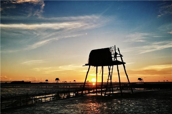 Cận cảnh mộtchòi canh ngao khi mặt trời vừa nhô khỏi mặt nước xa xa ngoài biển, bình minh đã lên khởi đầungày mới.