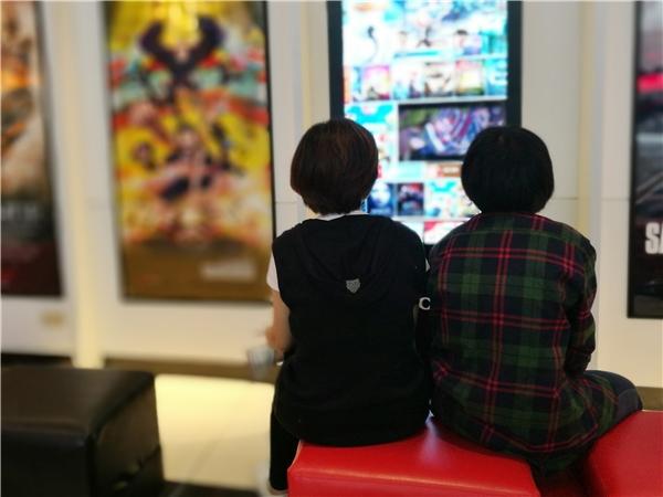 2 bạn trẻ ngồi chờ tới lượt xem đang ngó quatrailer Tấm Cám