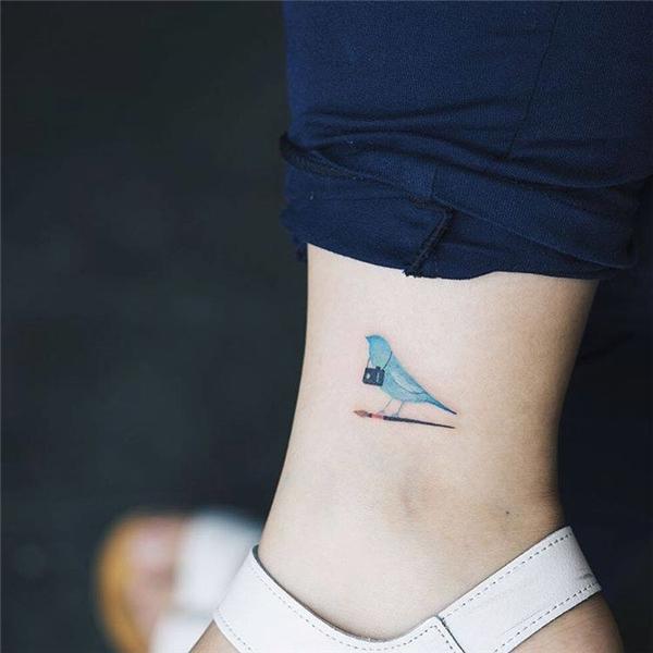Hình xăm chú chim xanh đeo túi sành điệu dành riêngcho những cô nàng mê làm đẹp.