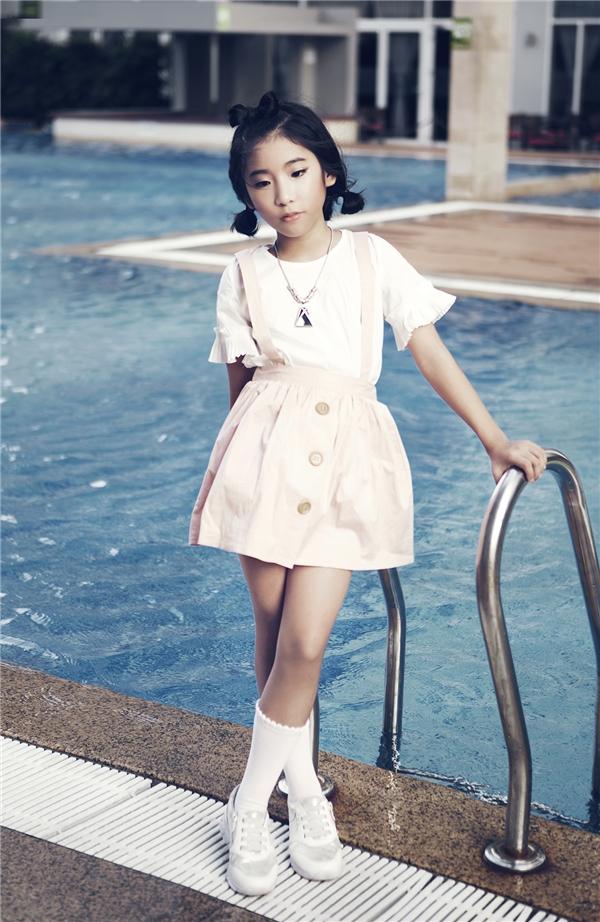Sắc hồng thạch anh ngọt ngào được Ju Uyên Nhi chọn kết hợp cùng tông trắng tinh khôi tôn lên nét trẻ trung, hồn nhiên của cô bé. Chiếc quần yếm cổ điển làm người xem gợi nhớ đến thời thơ ấu với những kỉ niệm êm đềm, đẹp đẽ.