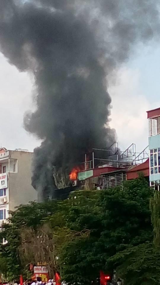 Một góc tòa nhà bốc lửa cháy ngùn ngụt gây hoảng loạn cho người đi đường. Ảnh: Hòai Nam