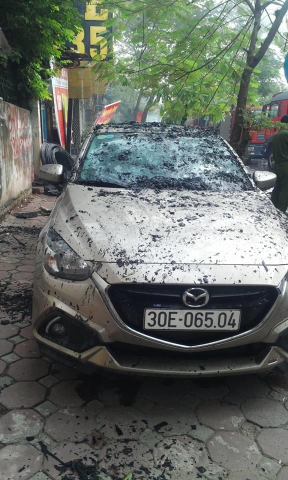 Một chiếc xe ô-tôđể trên vỉa hè cũng bị tàn tro củangọn lửa gây ảnh hưởng. Ảnh: Hoài Nam