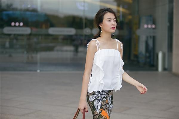Nữ ca sĩ trở nên thanh lịch hơn với set trang phục chọn phối giữa chân váy bút chì họa tiết hoa nổi bật, trẻ trung cùng chiếc áo hai dây màu trắng tinh khôi, thanh khiết. Đi kèm bộ trang phục của cô là chiếc túi Chanel có giá đắt đỏ.