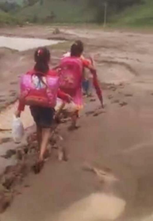 Hình ảnh các em học sinh vượt đường bùn lầy ngập ngụa sau cơn mưa để đến trường đã khiến nhiều cư dân mạng xúc động.