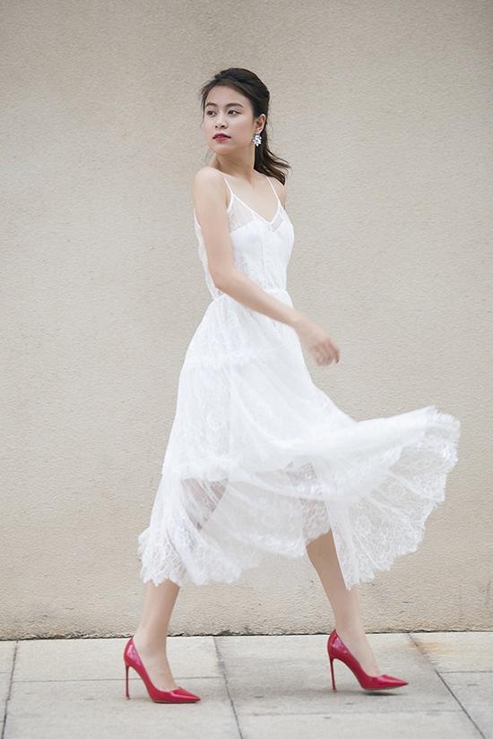 Hoàng Thùy Linh mang đến cảm giác nhẹ nhàng, thoải mái khi diện chiếc đầm trắng trên nền chất liệu ren, voan mềm mại. Đôi giày với sắc đỏ nổi bật trở thành điểm nhấn thú vị khiến người xem khó thể rời mắt.