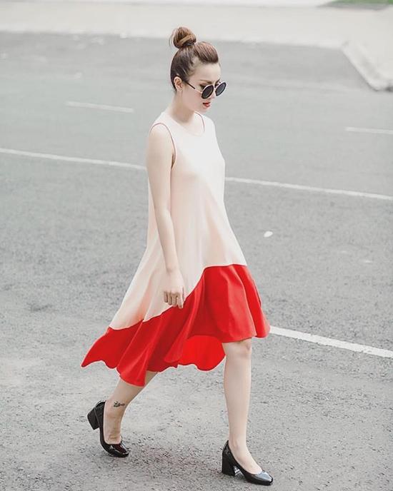 Với bộ váy chữ A phom rộng mềm mại, Yến Nhi trông trẻ trung hơn nhờ sắc cam hồng pastel kết hợp tông đỏ cam nồng nàn, nổi bật.