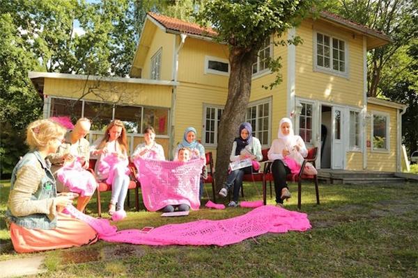 Những người phụ nữ Syria và Ukraina đang hỗ trợ Olek đan tấm mành màu hồng.