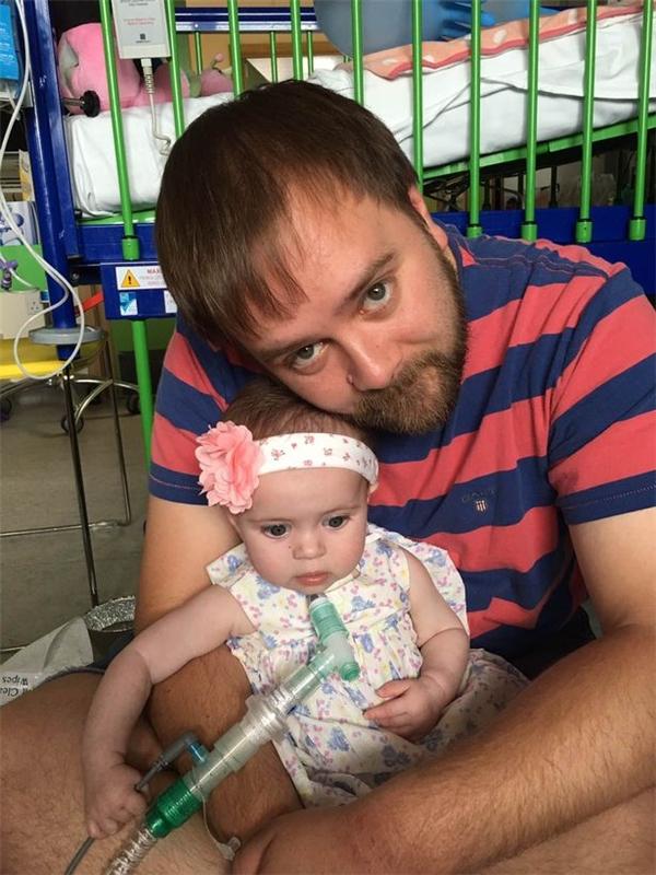 Cô bé trông khákhỏe khoắn và lanh lợitrong vòng tay của bố.