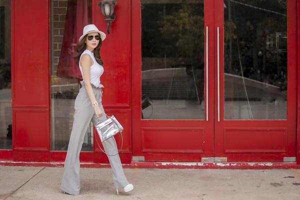 """Để tránh tạo cảm giác """"hầm hố"""" từ những đôi giày đế """"khủng"""", Ngọc Trinh thường chọn quần dài ống rộng, khéo léo che khuất gót nhọn."""