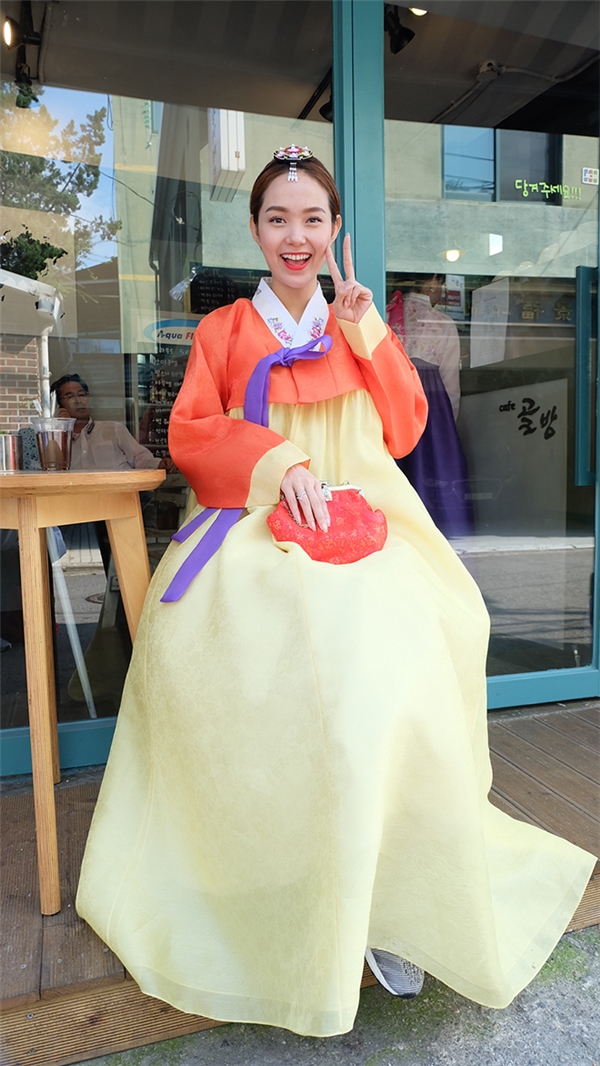 Trong chuyến tham quan, Minh Hằng diện hanbok truyền thống với hai sắc màu cam, vàng làm chủ đạo. Tuy nhiên, nữ ca sĩ lại mang giày thể thao năng động, trẻ trung trông khá lạ mắt.