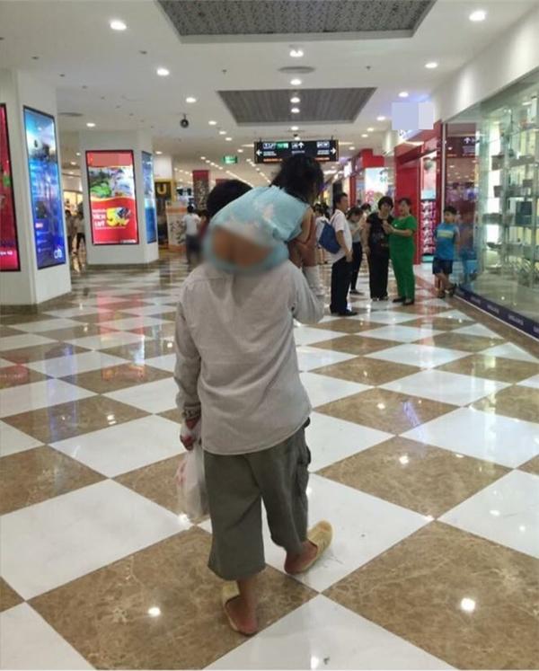 """Hình ảnh hai cha con """"ngây ngô"""" trong một trung tâm thương mại tại Hà Nội. (Ảnh: FB Đồ Rê Mi)"""
