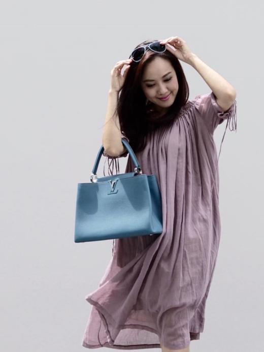 Chiếc túi hàng hiệu Louis Vuitton được cô mix với chiếc đầm suôngthoải mái ra phố.