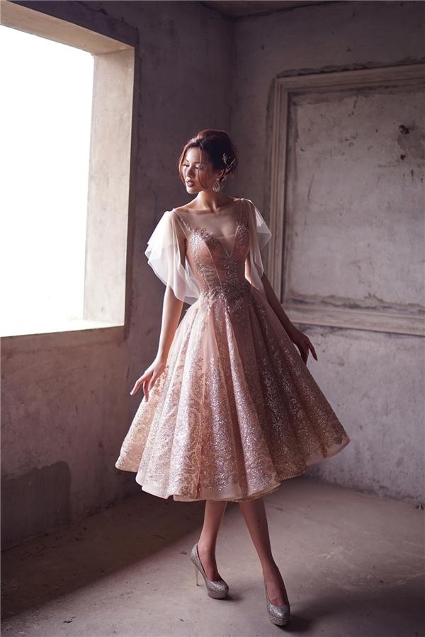 Thiết kế váy xòe điệu đà, nhẹ nhàng được tạo điểm nhấn bằng những chi tiết ánh kim bắt mắt, nổi bật. Khả Trang trông tựa như những nàng công chúa bước ra từ các mẩu chuyện thần thoài gắn liền với thuở ấu thơ của mỗi con người.
